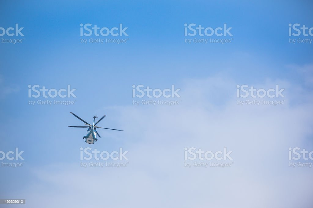Helicopter Flying Away in Distant Sky stock photo