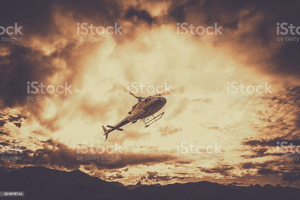 Helicopter Flying in Mountains With Dark Clouds stock photo