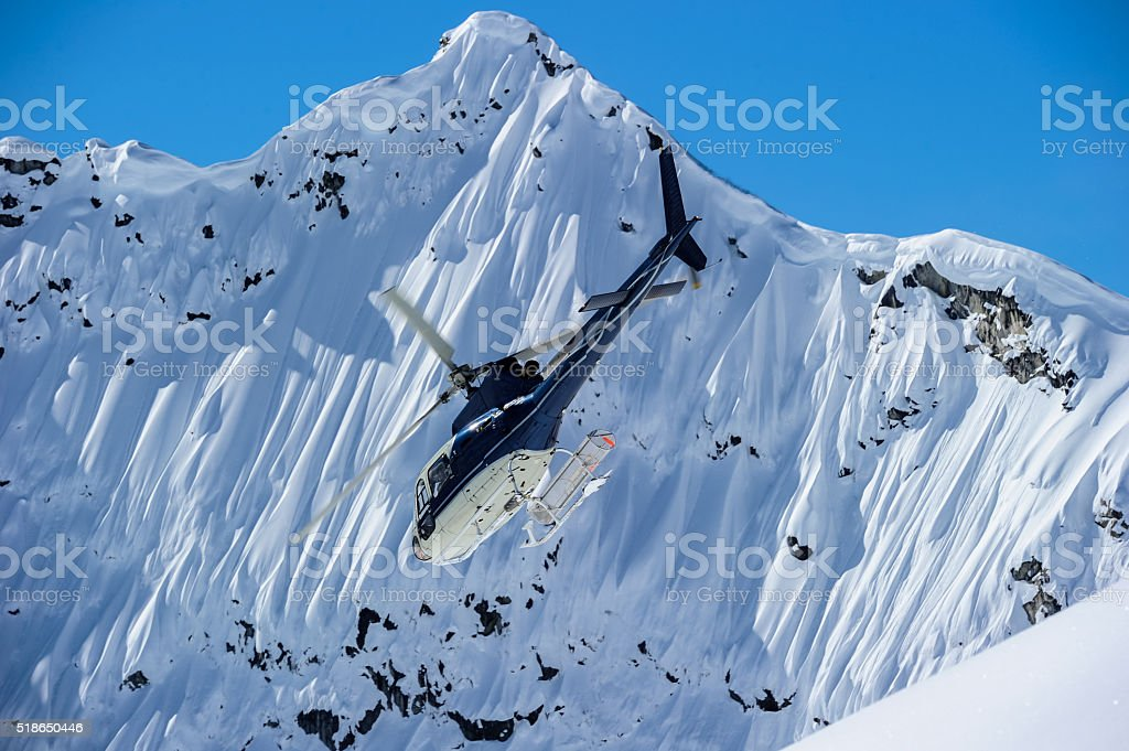 Helicopter flying in the mountains stock photo