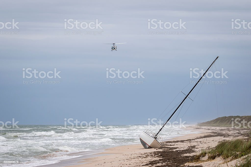 Helicopter Flying Over a Stranded Sailboat on a Florida Beach stock photo