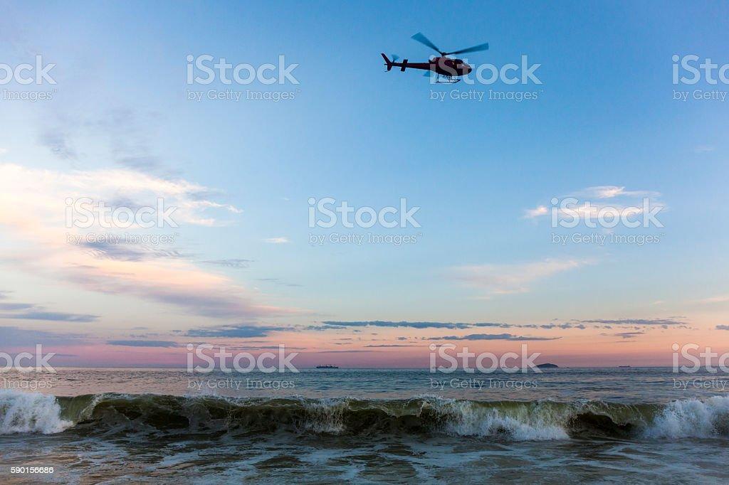 Helicopter flying over Copacabana Beach at sunset, Rio de Janeiro stock photo