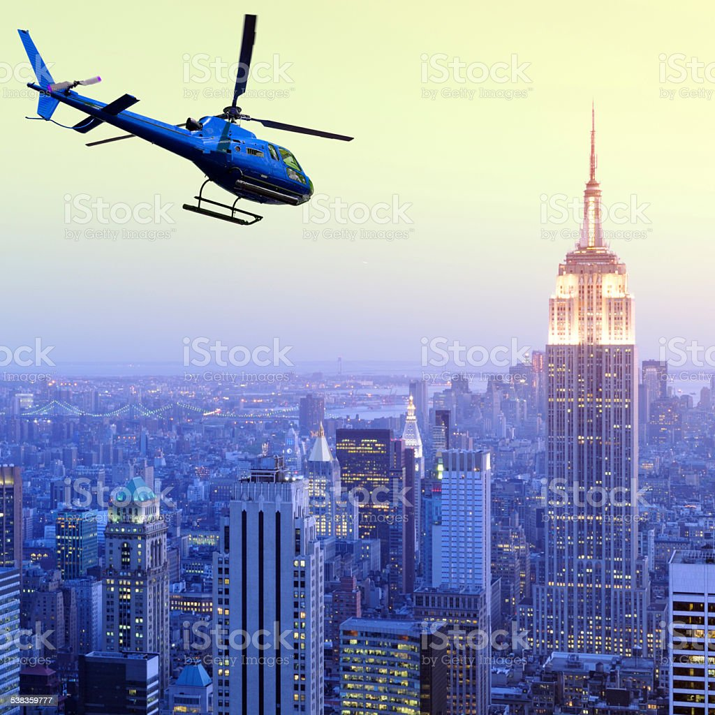 Helicopter flying over Empire State Building, NYC. Aerial View. stock photo