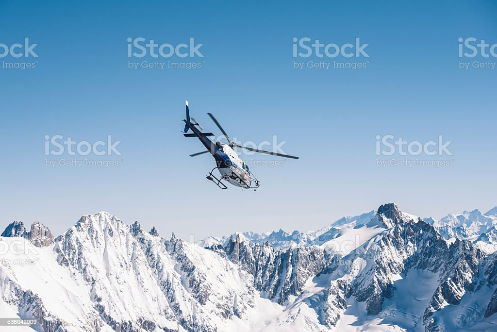 Helicopter flying over the Alps stock photo