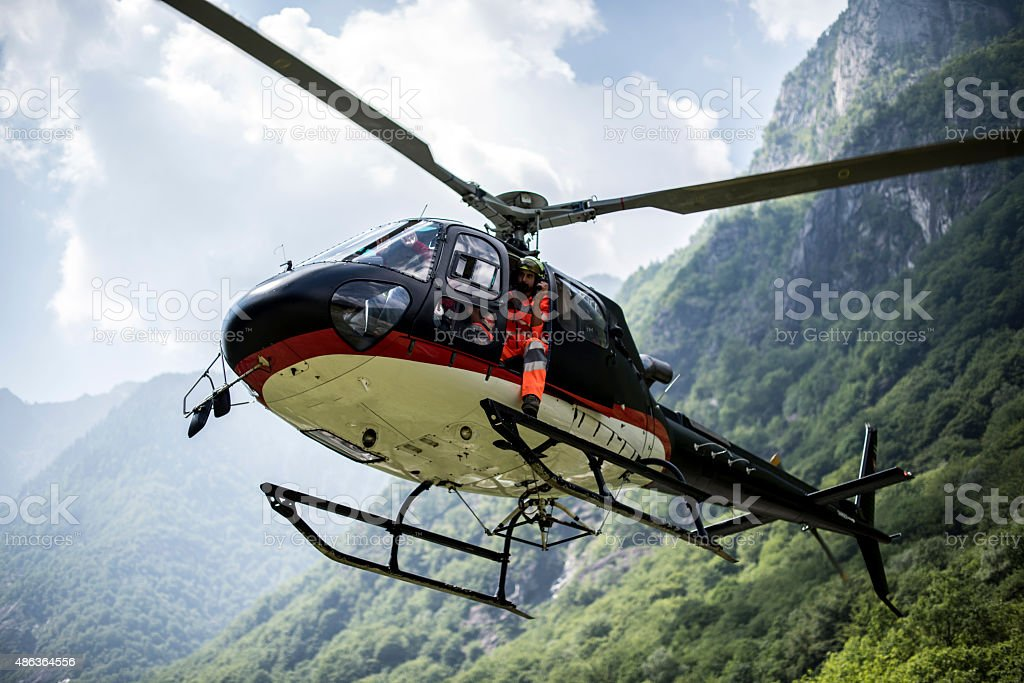 Helicopter hovers above grassy landing area stock photo