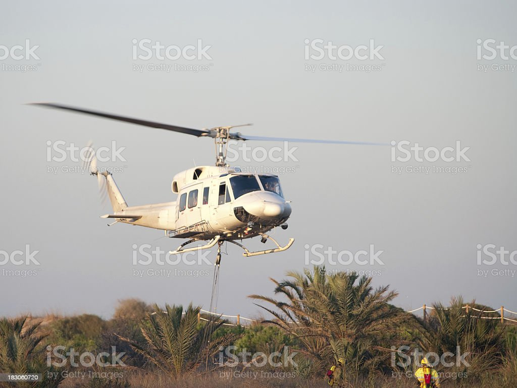 Helicopter hovers close to fireman stock photo