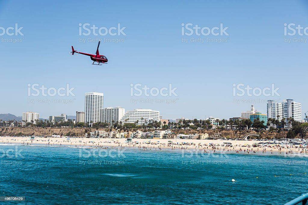 Helicopter hovers over busy Santa Monica Beach, California royalty-free stock photo