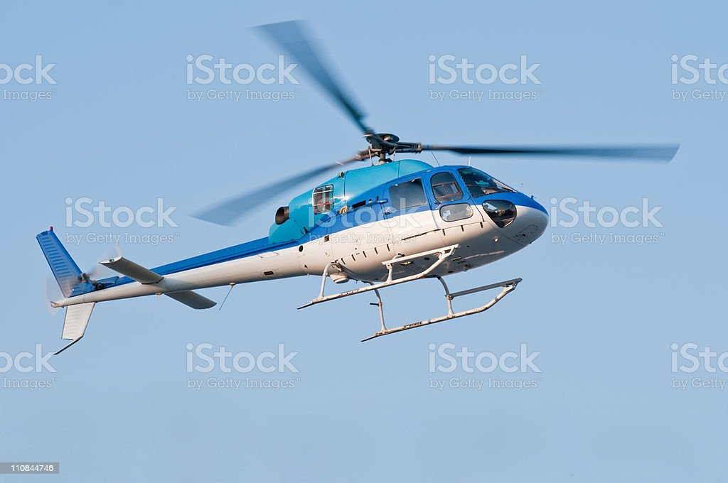 Helicopter in flight against blue sky stock photo