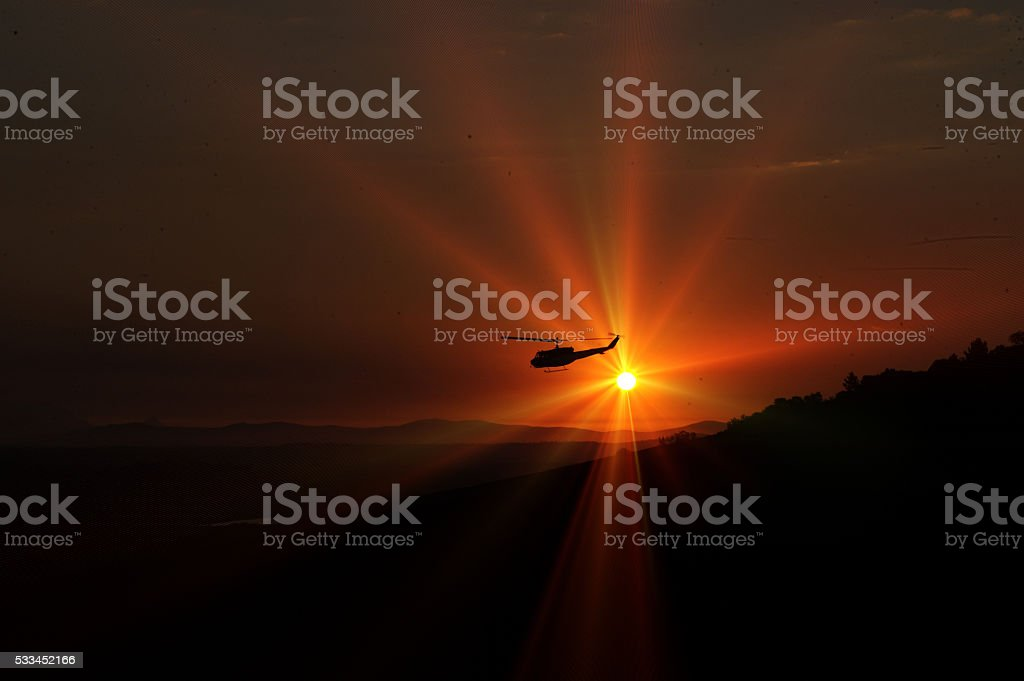Helicopter in flight at blazing sunset stock photo
