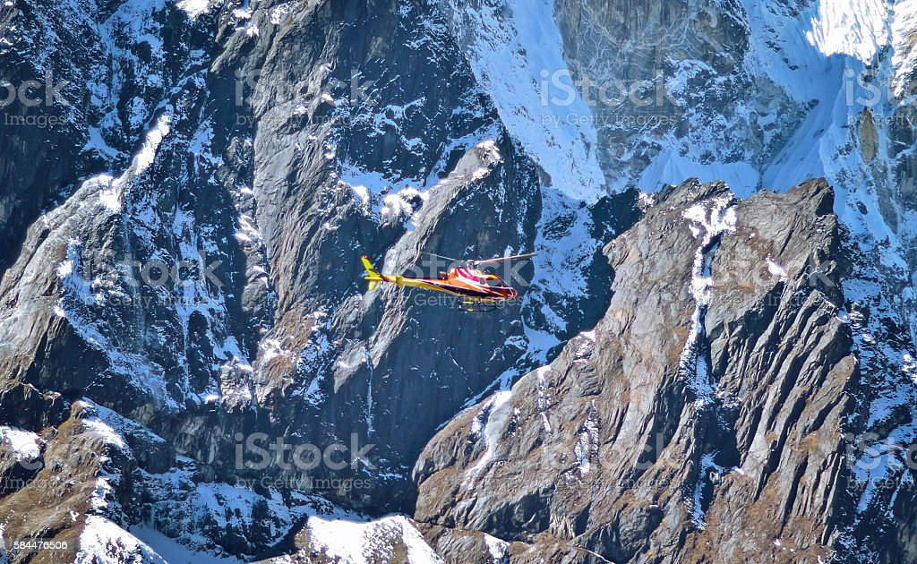 Helicopter is flying between snow mountains peak stock photo