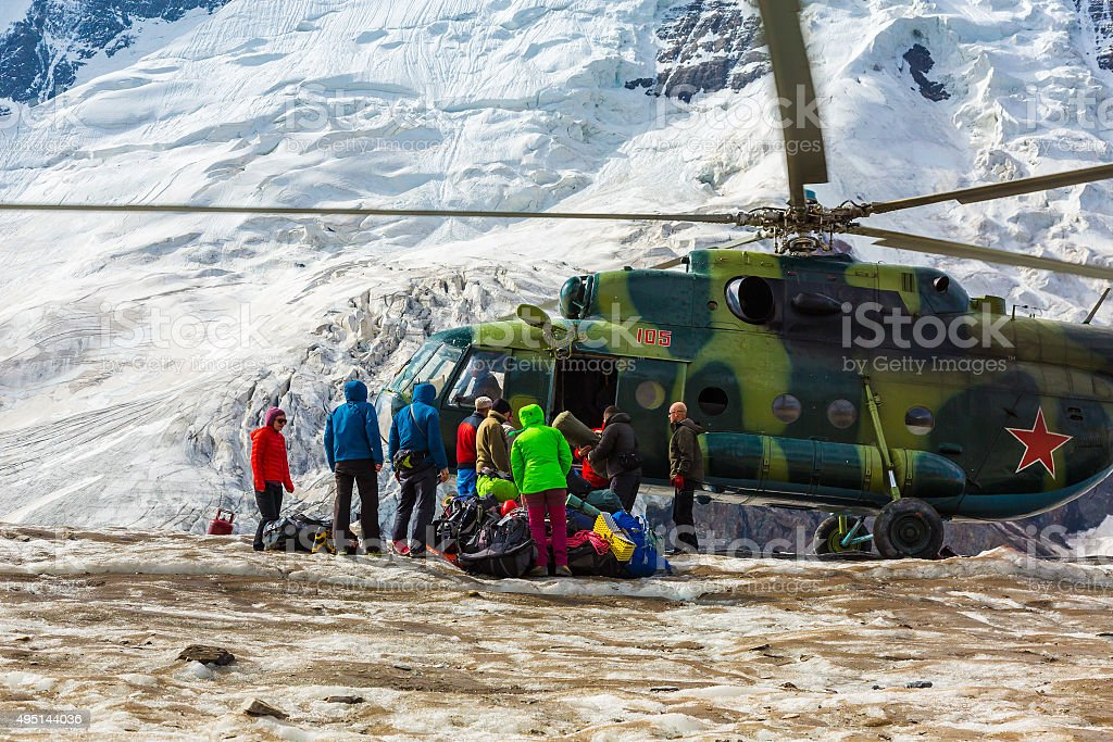Helicopter Landing on Ice Field Massive Glacier People Unloading Luggage stock photo