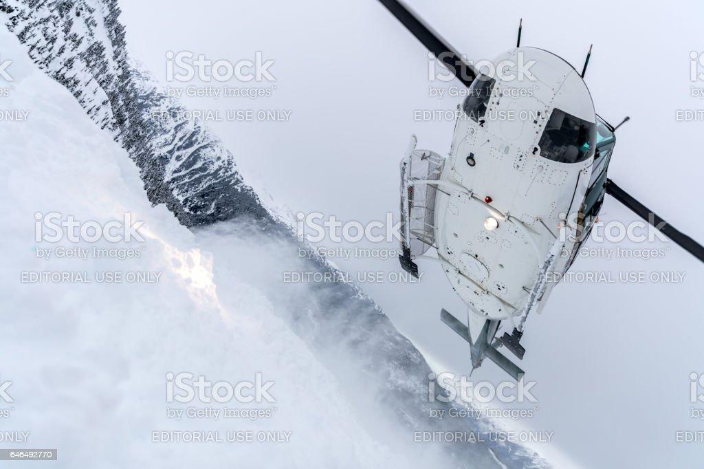 Helicopter Landing on Mountain Summit, Heli-Skiing stock photo