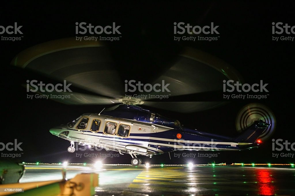 Helicopter landing on oil and gas platform stock photo