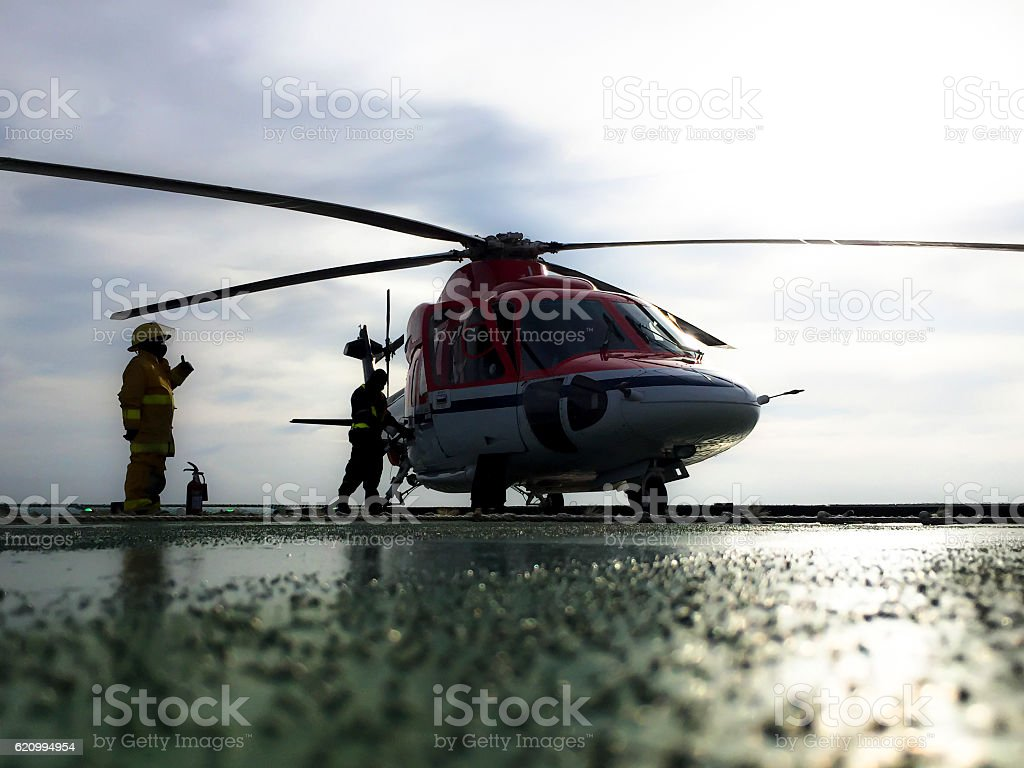 Helicopter on an oil platform being refueled stock photo