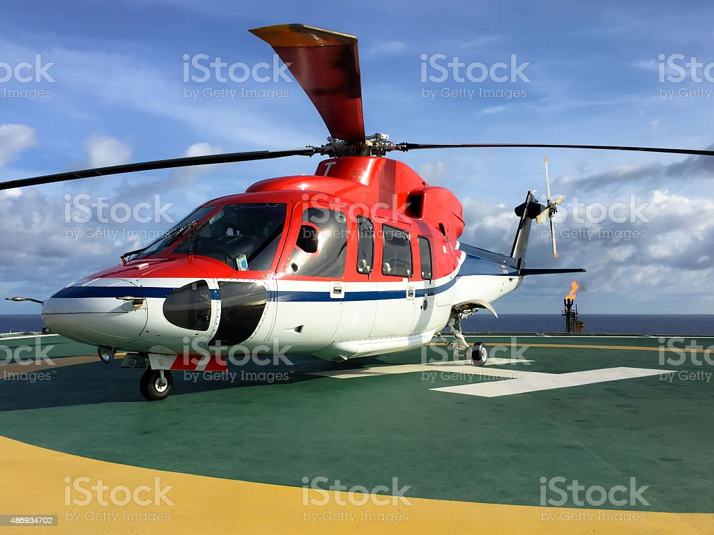 Helicopter Parked On An Oil Rig Platform Offshore stock photo