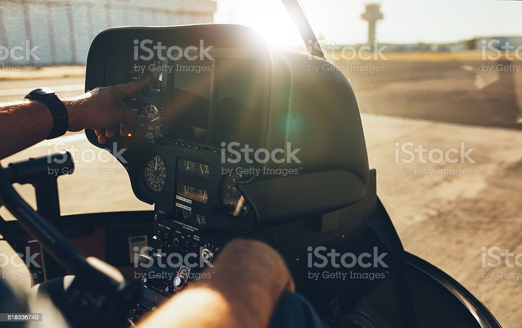 Helicopter pilot checking gauges on the instrument panel stock photo