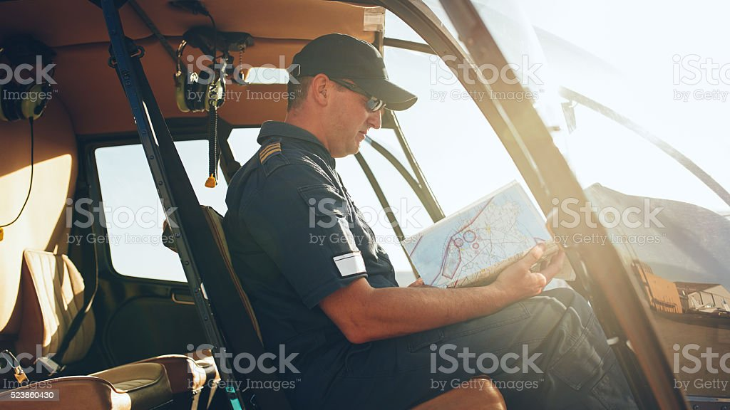Helicopter pilot reading flight map stock photo