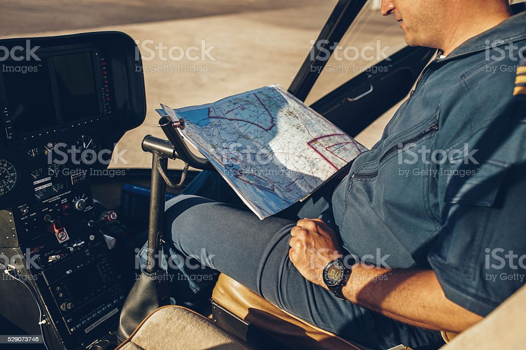Helicopter pilot reading map. stock photo