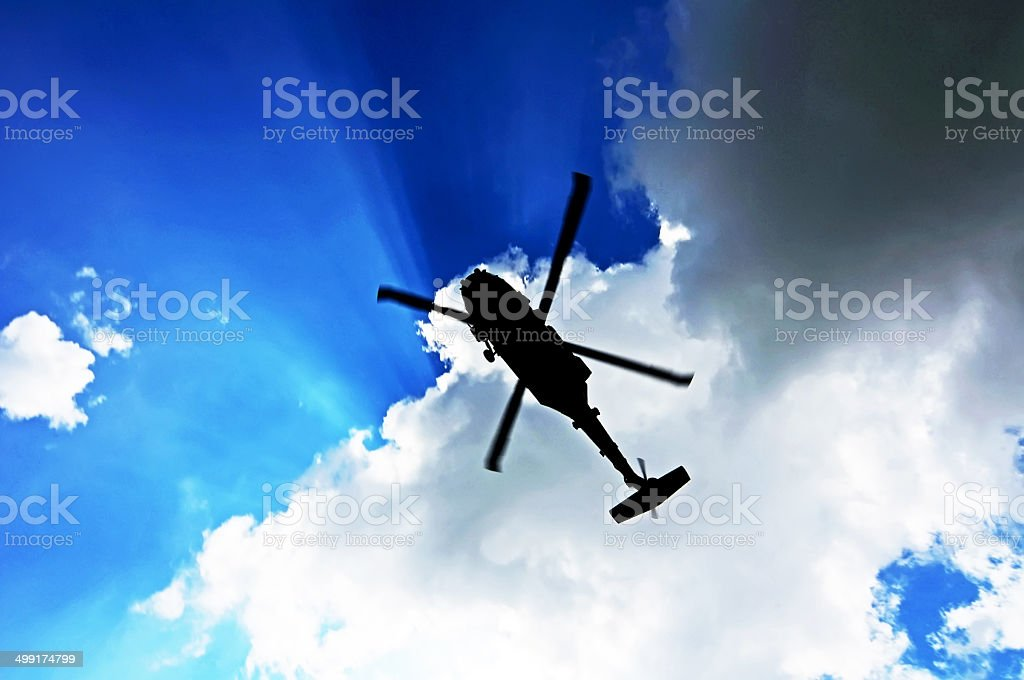 Helicopter silhouette against the sky stock photo
