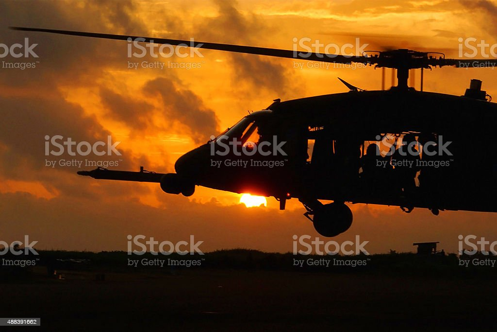 Helicopter soldiers at sunset stock photo