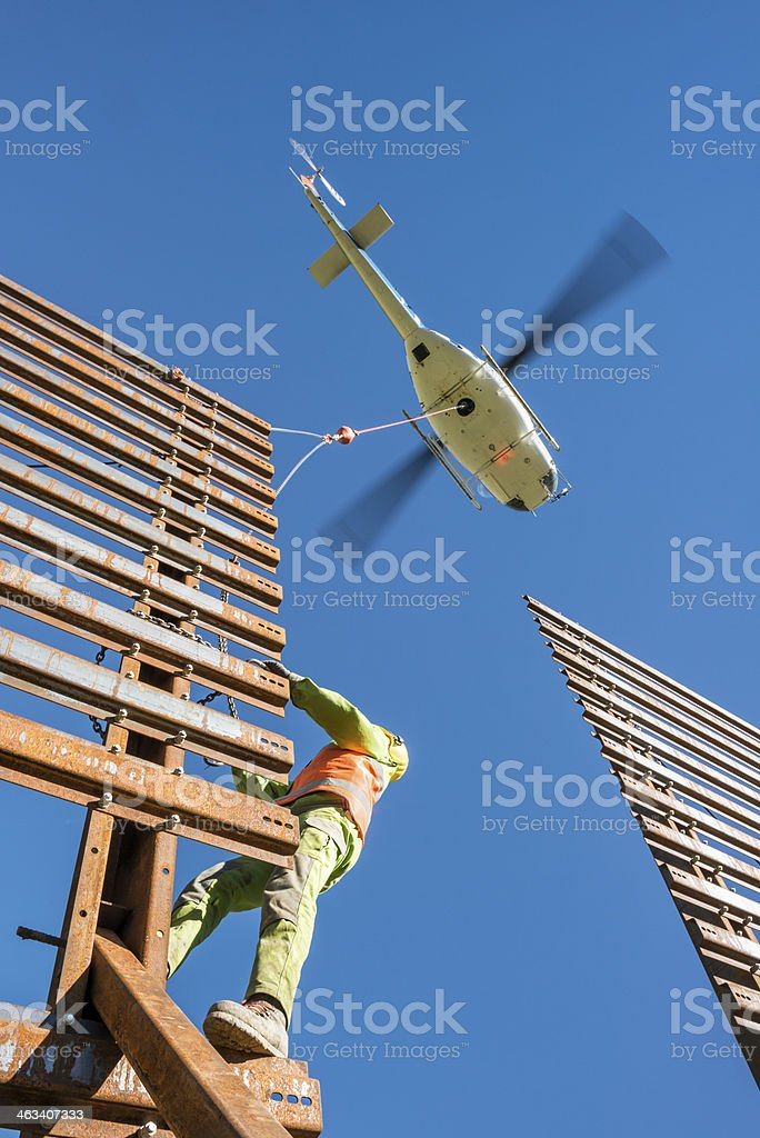 helicopter transporting steel wall to mechanic at site stock photo