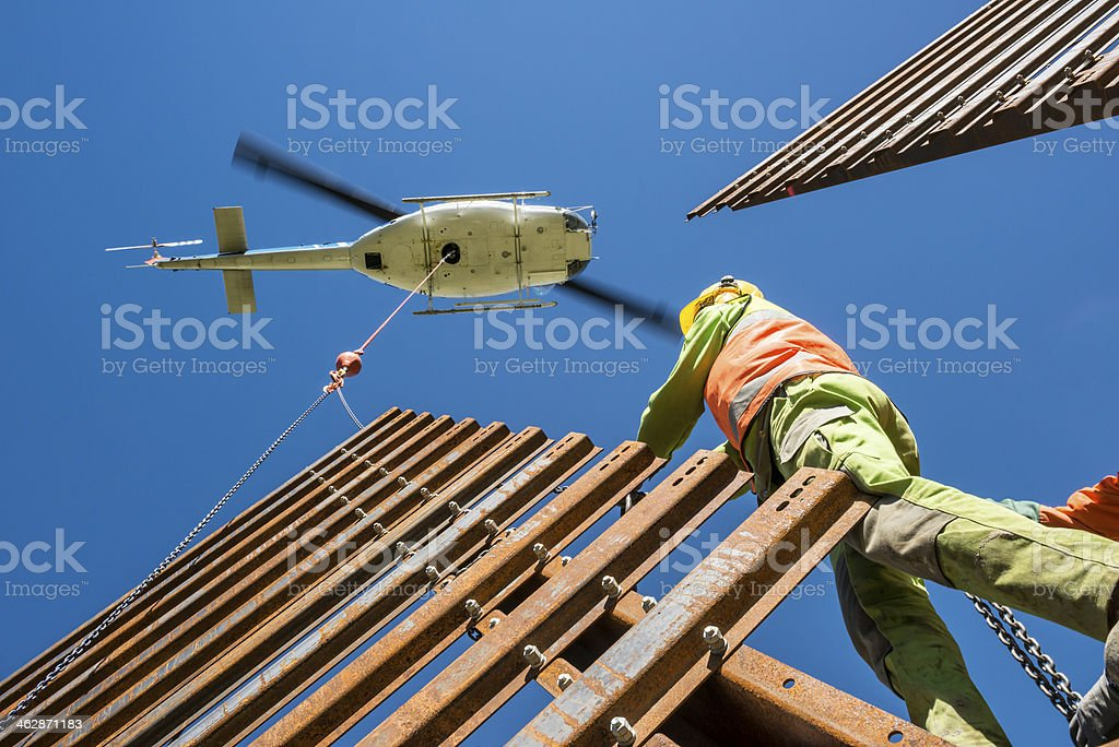 helicopter transporting steel wall to mechanic stock photo
