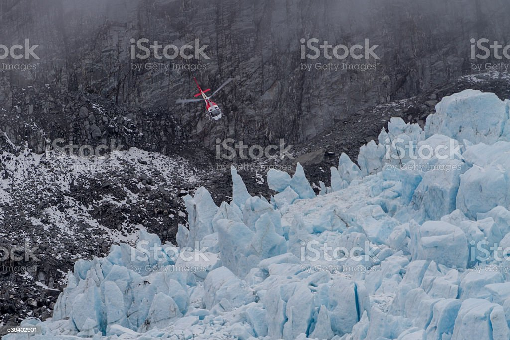 Helicopter trying to land on a Glacier. stock photo