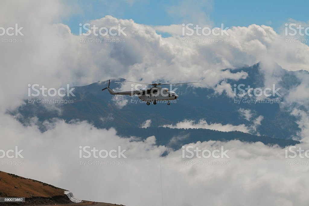Helicopter with cargo cable and mountains in clouds stock photo