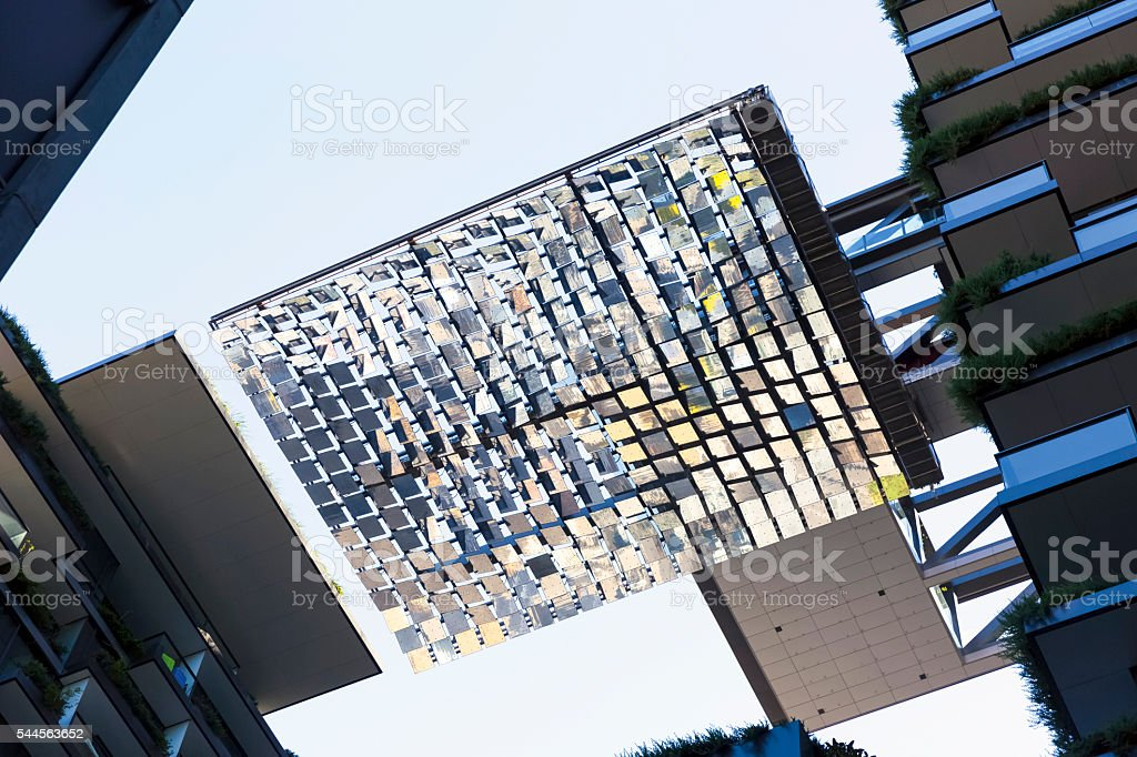 Heliostats, low angle view, motorised mirrors on high rise building stock photo