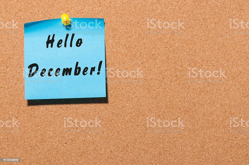 Hello December written on blue paper pinned at cork notice stock photo