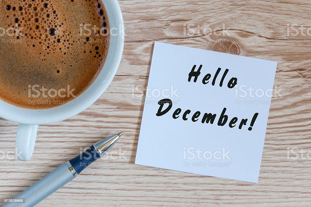 Hello December written on paper near morning coffee cup at stock photo