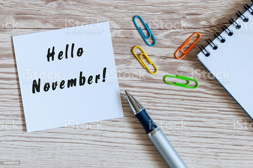 Hello November. hand drawn lettering on notepad at the workplace stock photo
