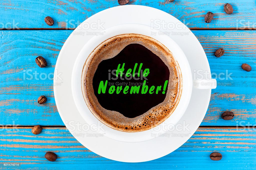 Hello November written on coffee cup at blue wooden surface stock photo