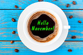 Hello November written on coffee cup at blue wooden surface