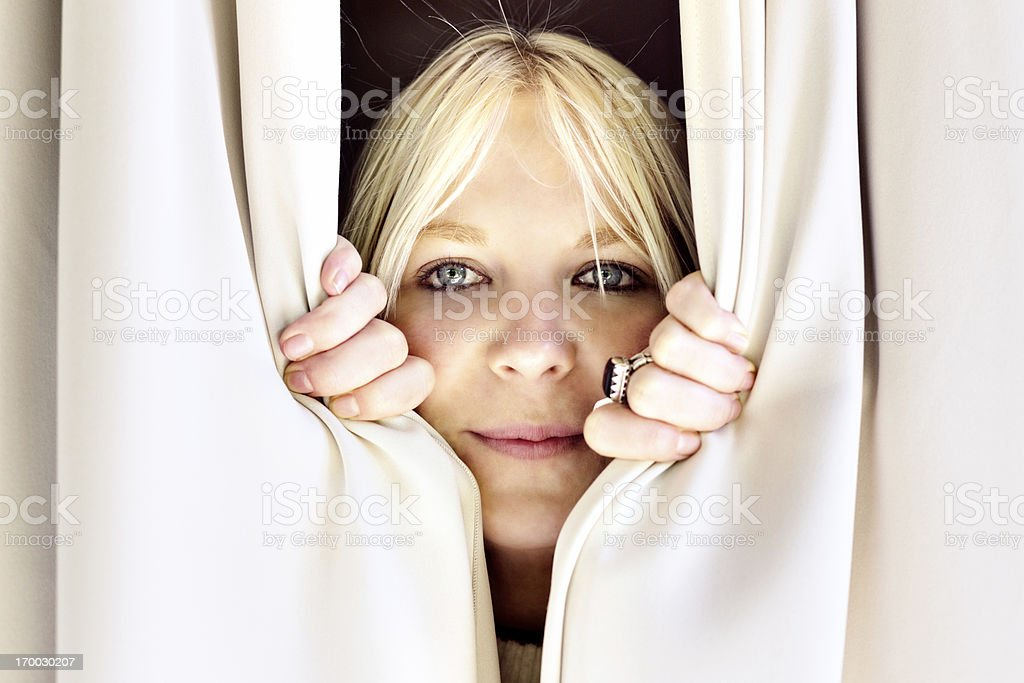 Hello there Cute blonde peeping through curtains and smiling royalty-free stock photo