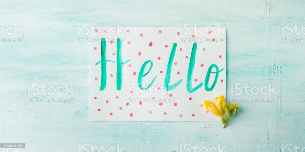 Hello word spelling by watercolor hand lettering yellow flowers stock photo