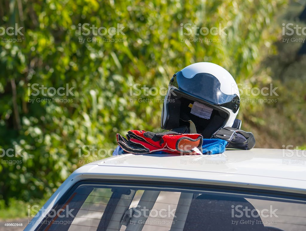 helmet and gloves on a car rooftop stock photo