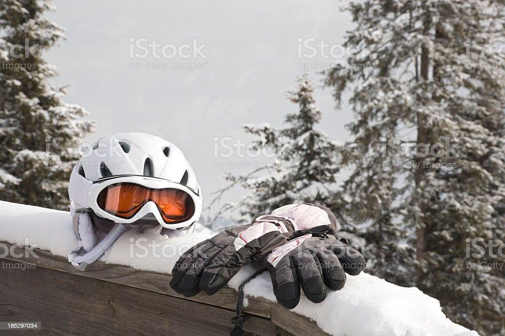 A helmet and gloves on a snowy railing near trees stock photo