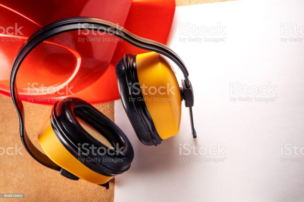 Helmet, earphones and blank sheet of paper stock photo