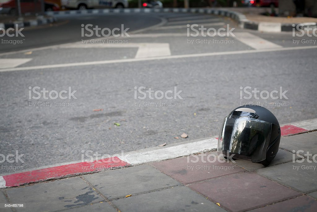 Helmet on sidewalks with background is blur of street. stock photo