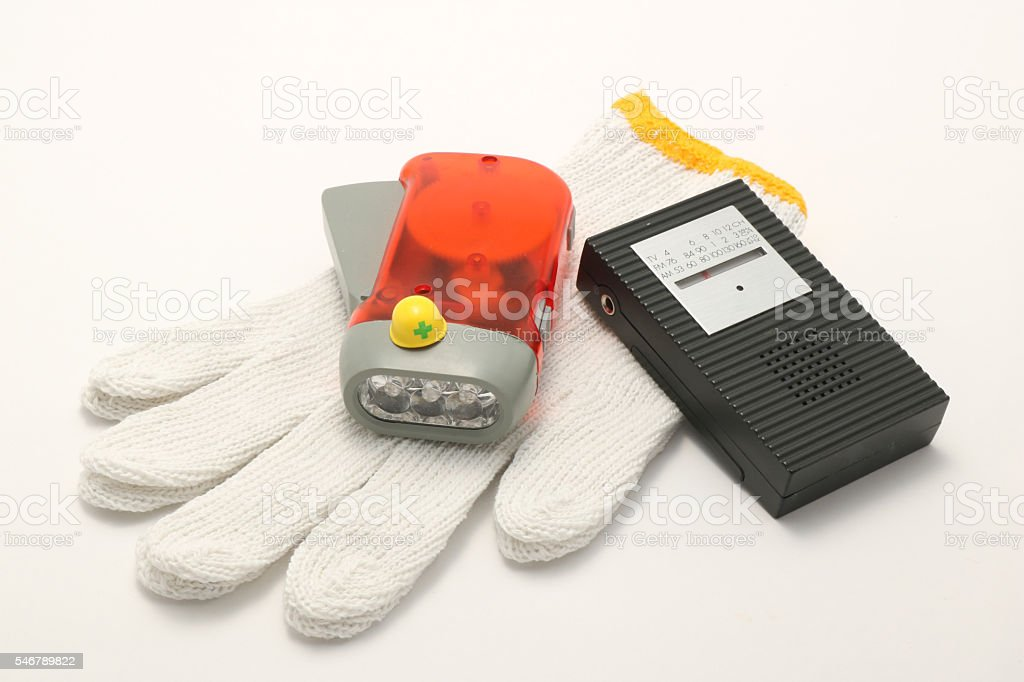 Helmet, portable radio, work gloves, and flashlight on white background. stock photo