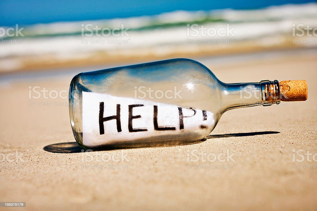 Help says frantic message in bottle on deserted beach royalty-free stock photo