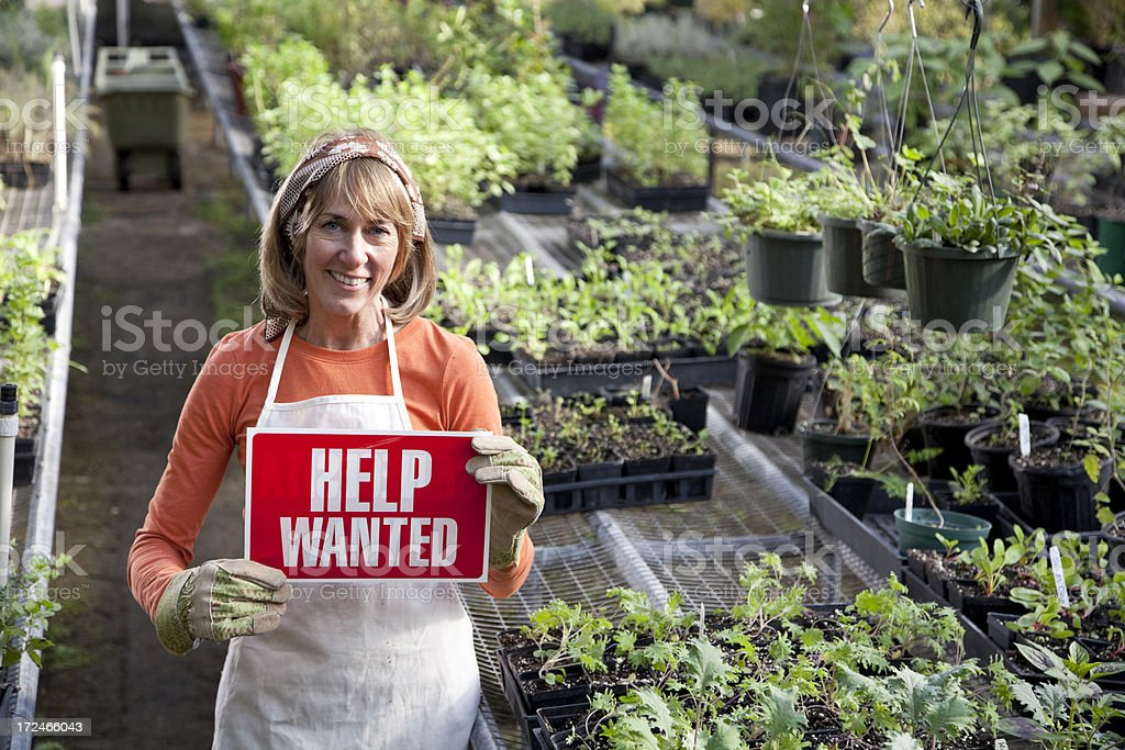 Mature woman in plant nursery holding HELP WANTED sign.