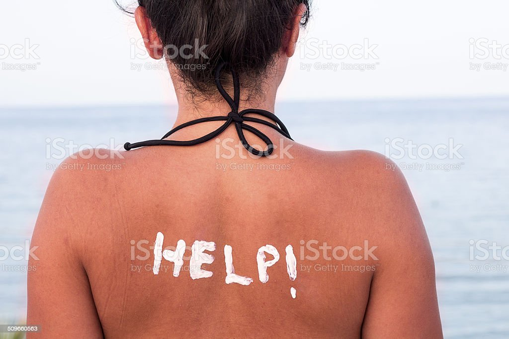 Help written with Sun Cream on a Woman's Shoulder stock photo