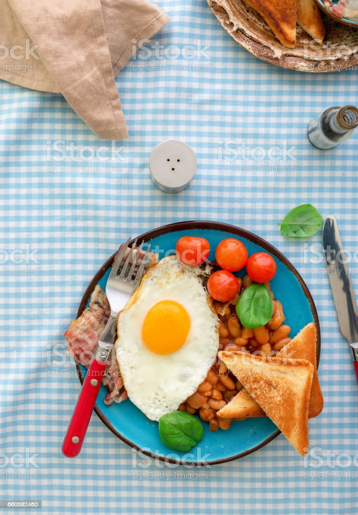 Helpful breakfast  - fried egg, beans, tomatoes, bacon and toast in a plate on table stock photo