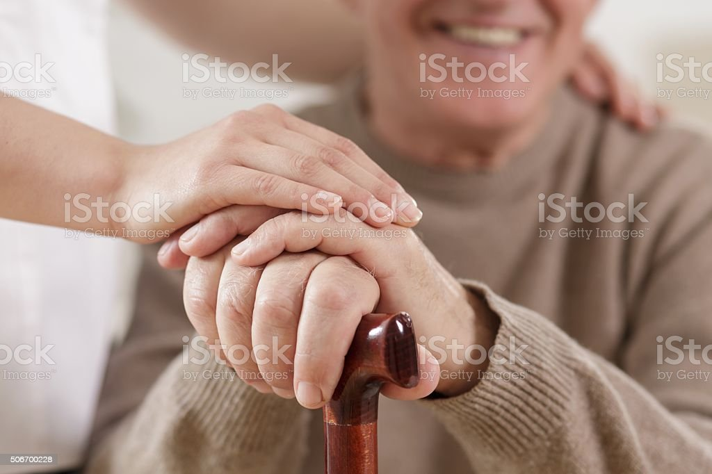 Helpful carer and happy old man stock photo