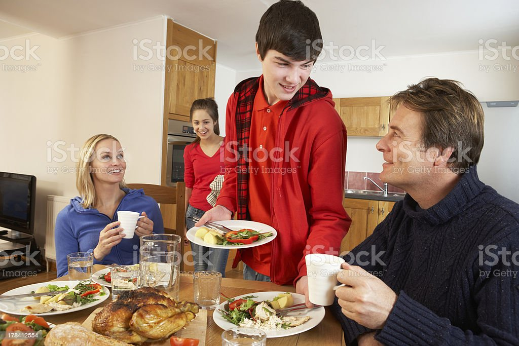 Helpful Teenage Children Serving Food To Parents In Kitchen royalty-free stock photo