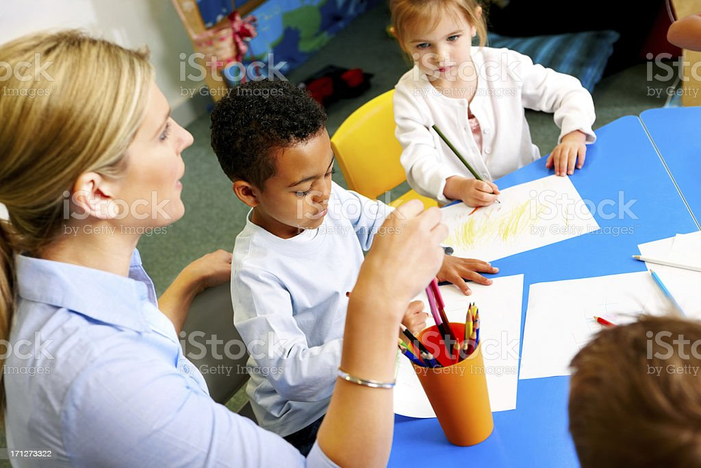 Helpful young teacher with preschoolers in class room royalty-free stock photo