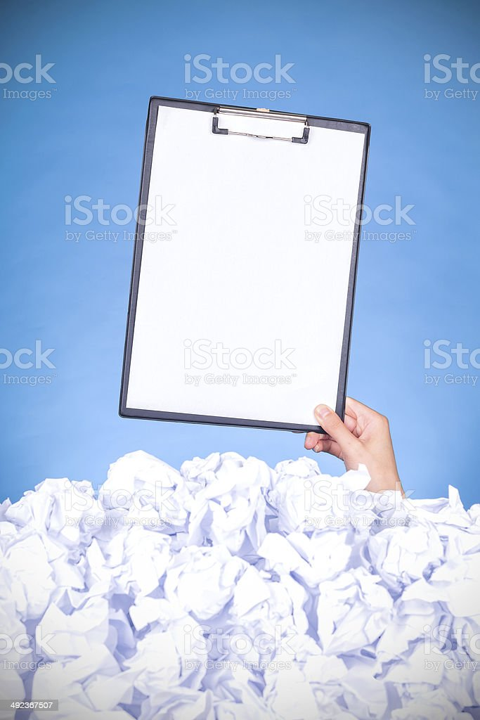 help:hand holding clipboard in crumpled pile of papers stock photo