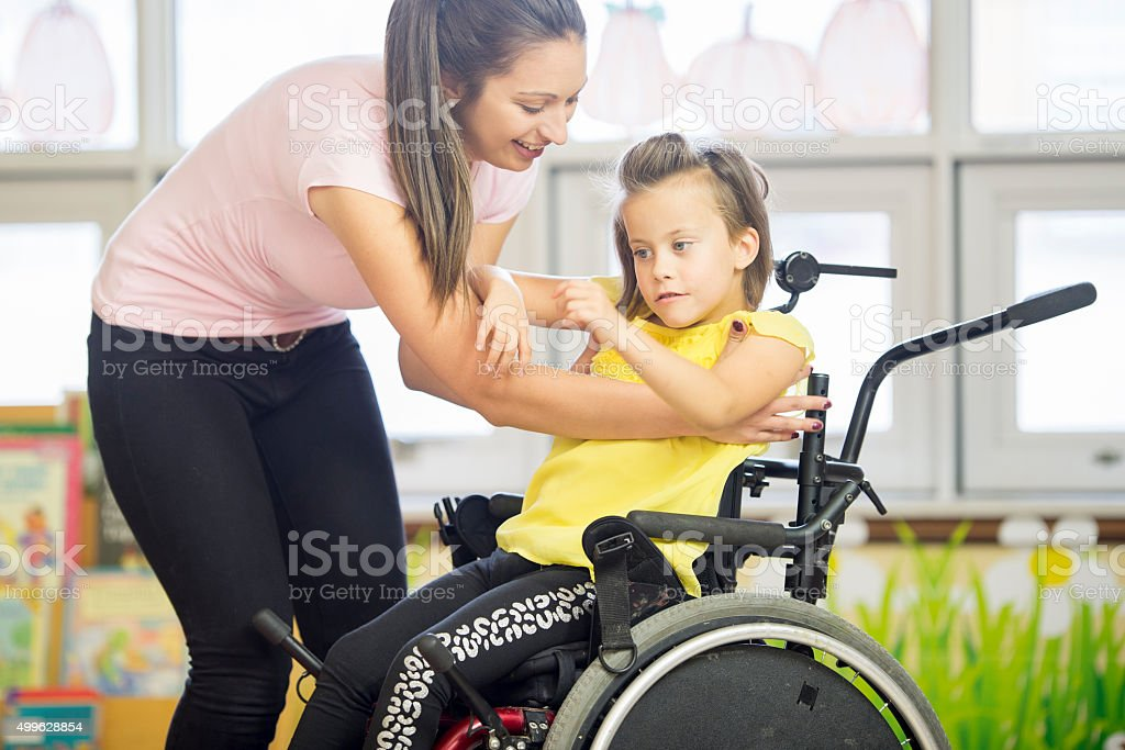 Helping a Child Out of Her Wheelchair stock photo