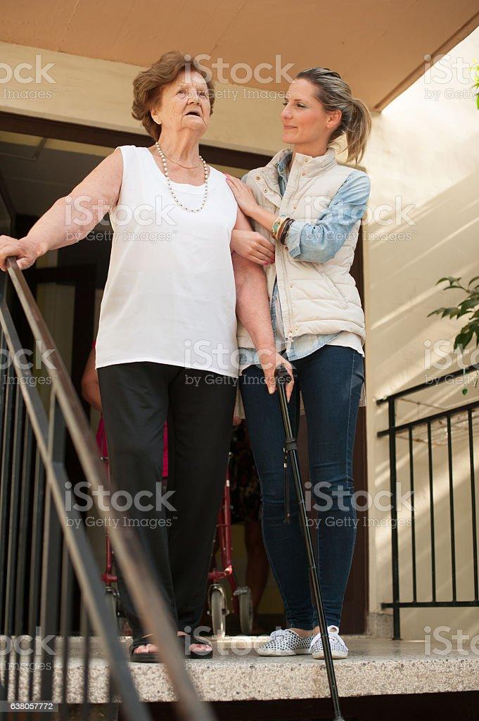 Helping an Elderly Woman Walk Downstairs stock photo